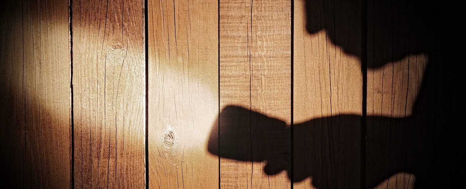 Human silhouette with flashlight in shadow on wood background,